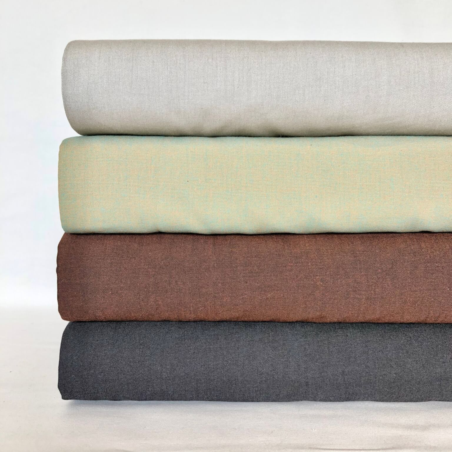 Four bolts of neutral color cotton fabric, stacked with gray on the bottom, then brown, then pale green, and then beige on top.