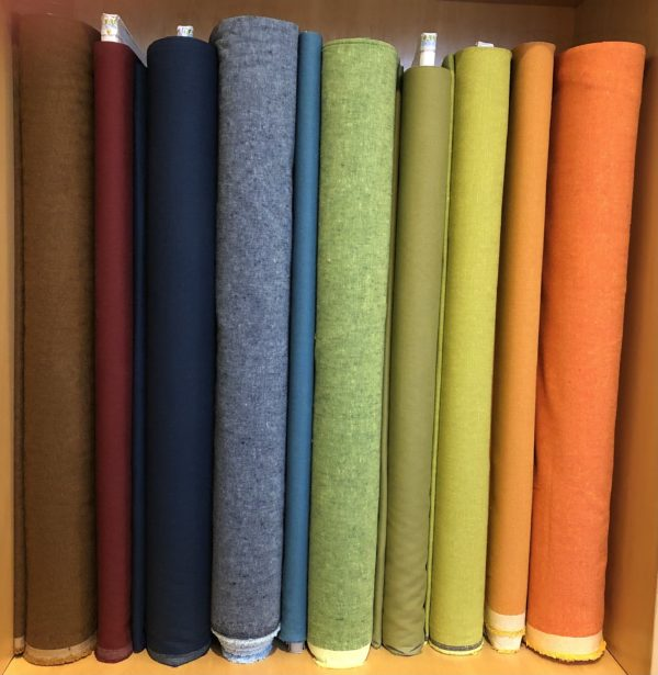 10 bolts of colorful Essex Linen on the shelf