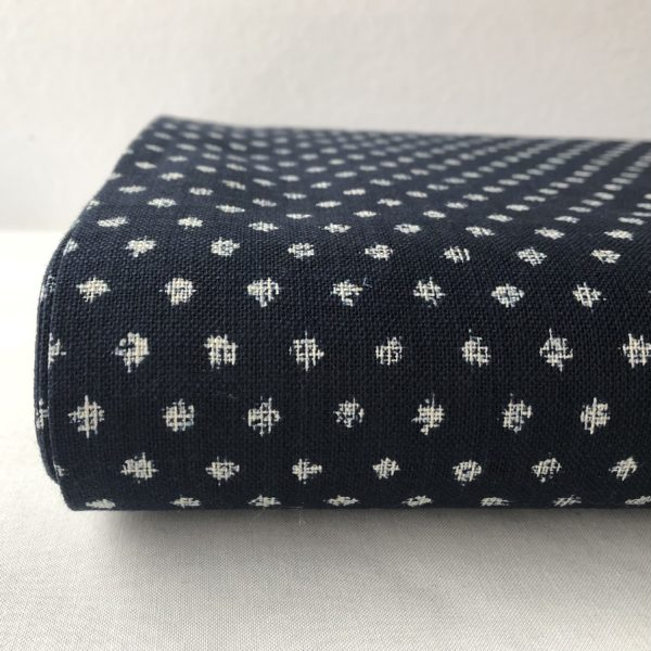 Close up of the end of a bolt of indigo blue homespun fabric with diagonally spaced dots