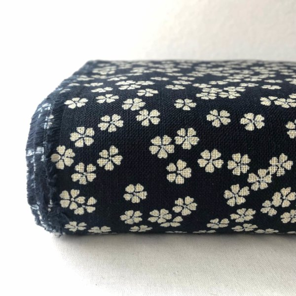 End of the bolt of dark indigo fabric printed with white cherry blossoms.