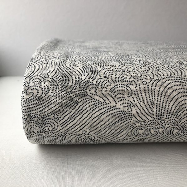 Close up of the end of a bolt of white homespun fabric printed with delicate, swirling waves