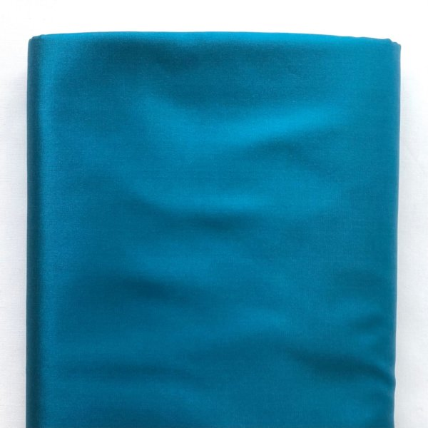 One end of a bolt of silky teal Radiance fabric.