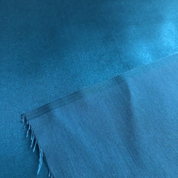 Silky teal Radiance fabric showing shiny silky front and matte, cottony back