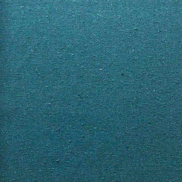 Close up of deep teal, slightly nubby silk fabric