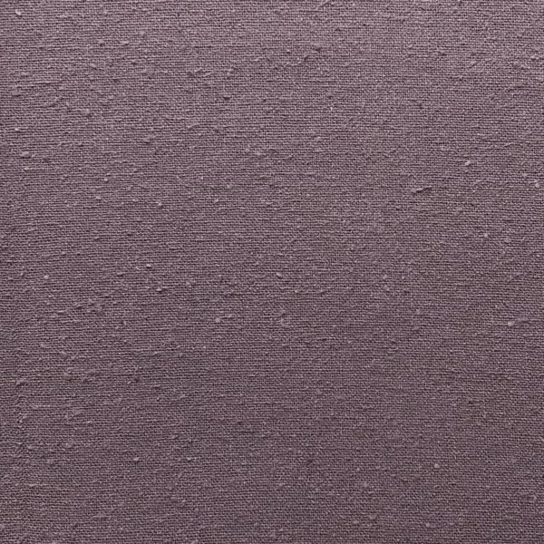 Close up of rich heather-mauve, slightly nubby silk fabric