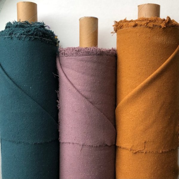 Three rolls of fabric - teal, mauve, and golden curry