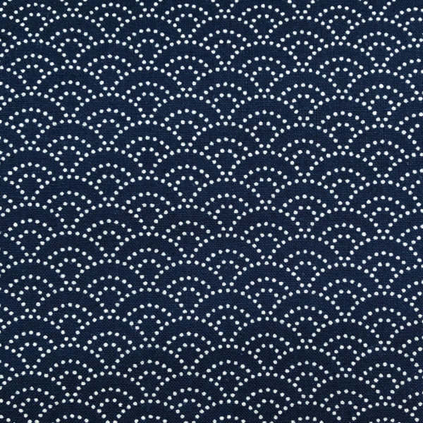 Indigo fabric with white dotted scalloped waves.