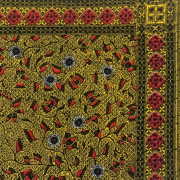 Close up of the corner of golden-yellow and red botanical print panel, bordered with red rosettes