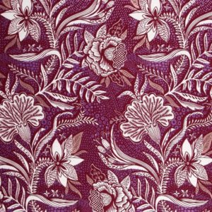 Maroon cotton fabric printed with highly detailed white flowers and purple metallic accents.