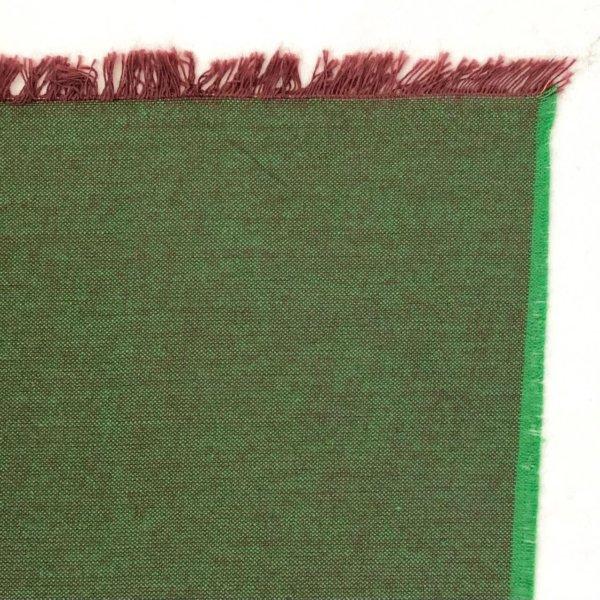 Fabric detail showing a bright green warp and dark, reddish-brown weft.