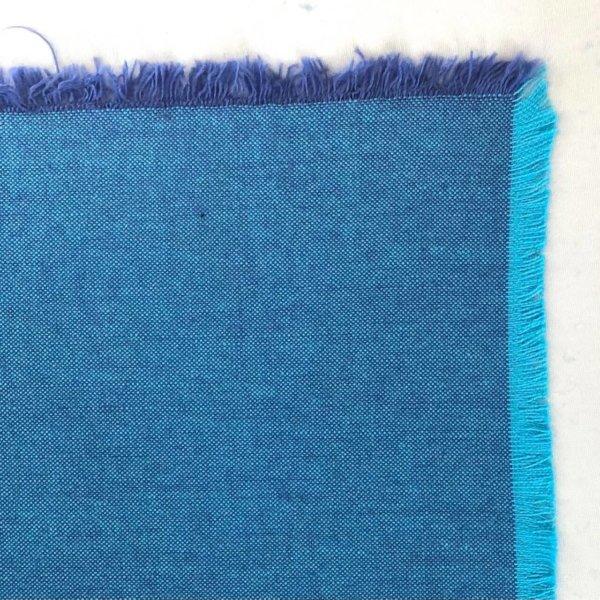 Fabric detail showing a bright turquoise warp warp and dark purplish blue weft.