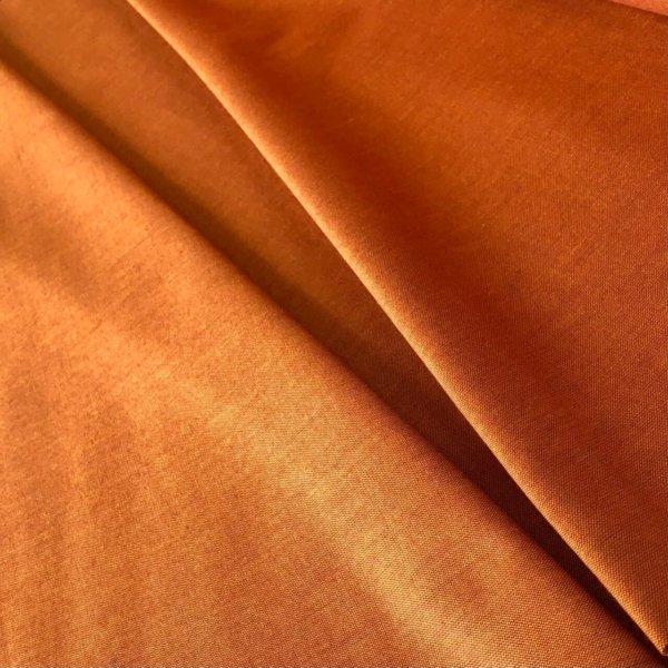 Earthy, orange colored fabric, pleated.
