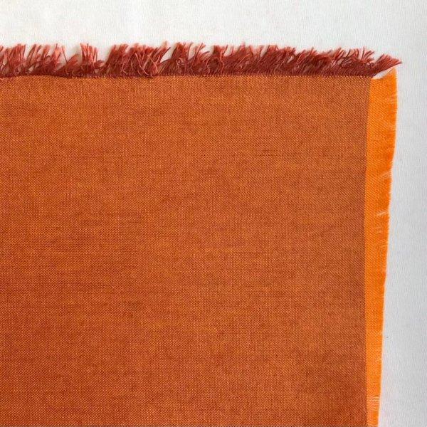 Fabric detail showing a carrot-orange warp warp and dark reddish brown weft.