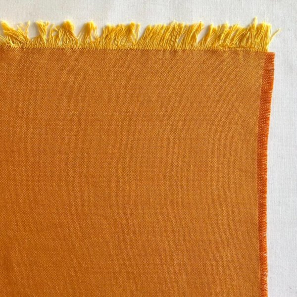 Fabric detail showing golden yellow warp and earthy orange weft.