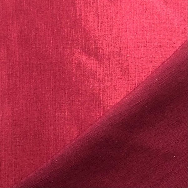 Close up of garnet red fabric, folded to show shiny silk front of fabric and matte back of fabric