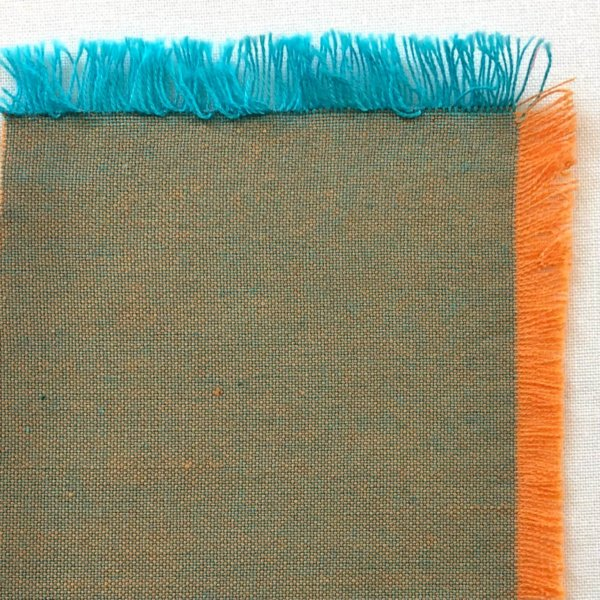 Neutral, putty-colored fabric composed of orange warp threads and a bright turquoise weft