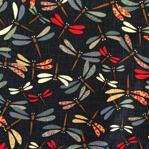 Closeup of fabric printed with festively colored, swirling dragonflies