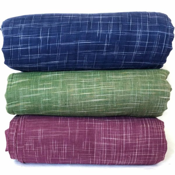 Stack of ikat crosshatched fabrics - indigo, green, and mulberry