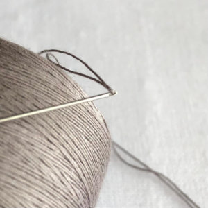 close up of threaded quilting needle
