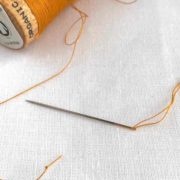 close up of threaded sewing needle