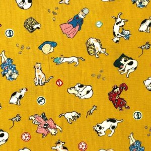 Closeup of golden yellow fabric printed with colorful kitties wearing traditional Japanese clothing.
