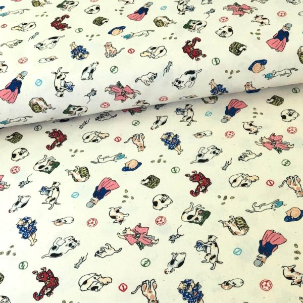 Closeup of white fabric printed with colorful kitties wearing traditional Japanese clothing.