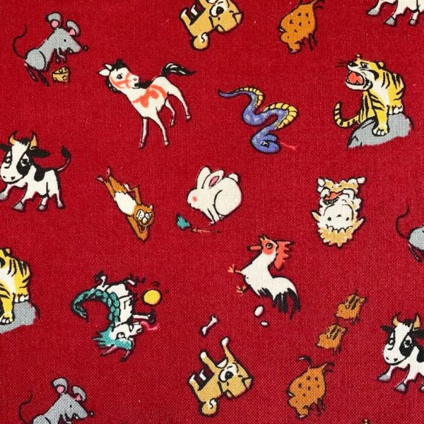 Closeup of red fabric printed with colorful animals of the Chinese Zodiac - Rat, Ox, Tiger, Rabbit, Dragon, Snake, Horse, Sheep, Monkey, Rooster, Dog and Pig.