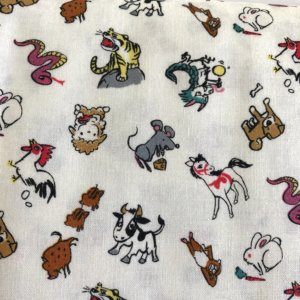 Closeup of white fabric printed with colorful animals of the Chinese Zodiac - Rat, Ox, Tiger, Rabbit, Dragon, Snake, Horse, Sheep, Monkey, Rooster, Dog and Pig.