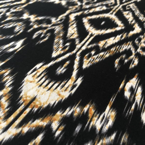 Black, highly detailed ikat print with cream and gold accent.