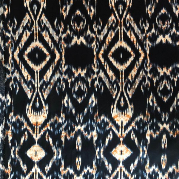 Dark blue, highly detailed ikat print with cream and orange accent.