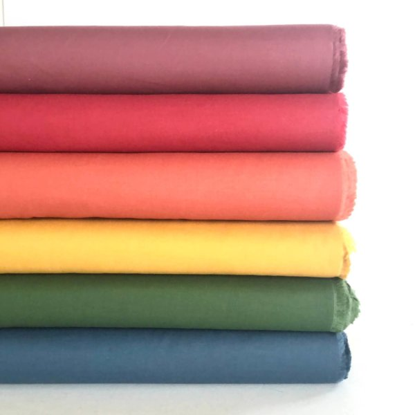Stack of solid Long Staple fabrics in a full rainbow spectrum of colors