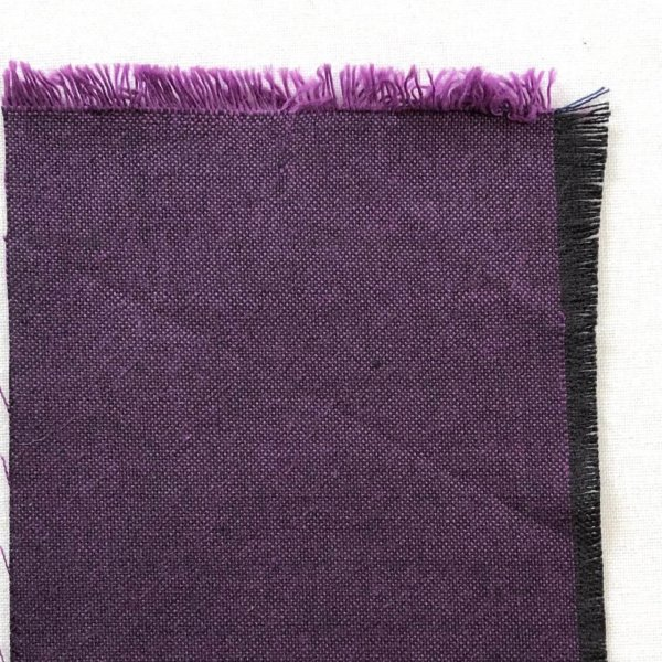 Swatch of purple fabric showing violet weft and black warp