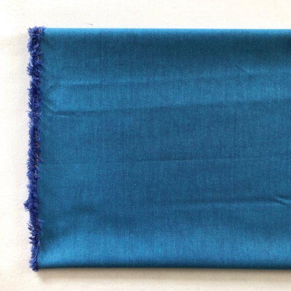 Medium blue fabric with edges frayed to show turquoise warp and purple weft