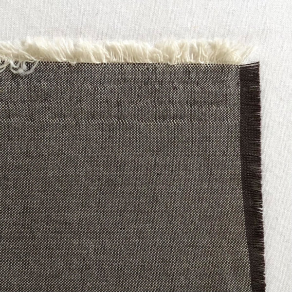 Swatch of gray fabric showing natural, off-white weft and darkest brown warp