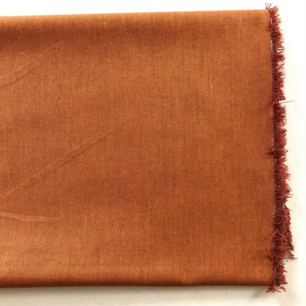 swatch of Rust peppered cotton showing copper weft and bright orange warp.
