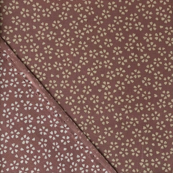 Pink fabric, densely printed with traditional white cherry blossoms and showing reverse side with brighter white blossoms
