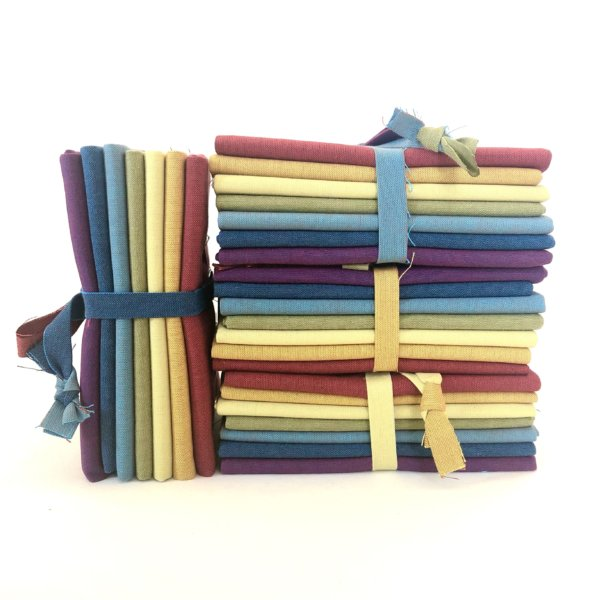 Stacked bundles, each containing a rainbow of colorful fat quarters.