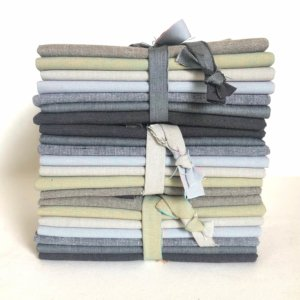 Stack of neutral colored, folded fat quarters in bundles.