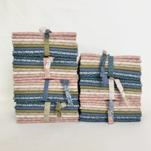 multiple bundles of Softly colored japanese fabrics.