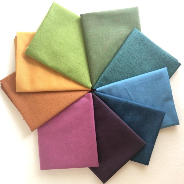 All nine colors of fabric arranged in a colorwheel