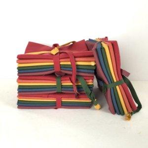 Stack of fat quarter bundles, each bundle has six fabrics - red, orange, yellow, green, blue, and mauve