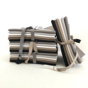 Stack of fat quarter bundles, each bundle has six fabrics - white, black, two grays, and two taupe-browns